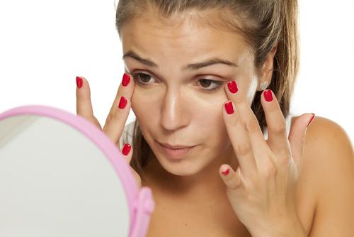 Mulher Puxa O Canto Dos Olhos E Olha Num Espelho. Parece Precisar De Nossas Dicas Simples Para Aliviar As Olheiras.