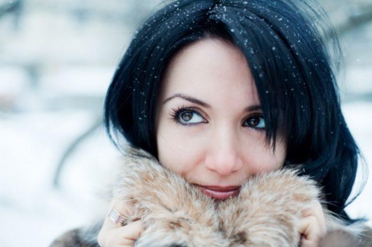 Mulher Com Casaco De Frio Na Neve Ilustra O Artigo Sobre Como Cuidar Da Pele No Inverno.